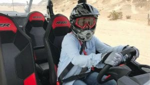 Photo of woman riding a RZR in the desert