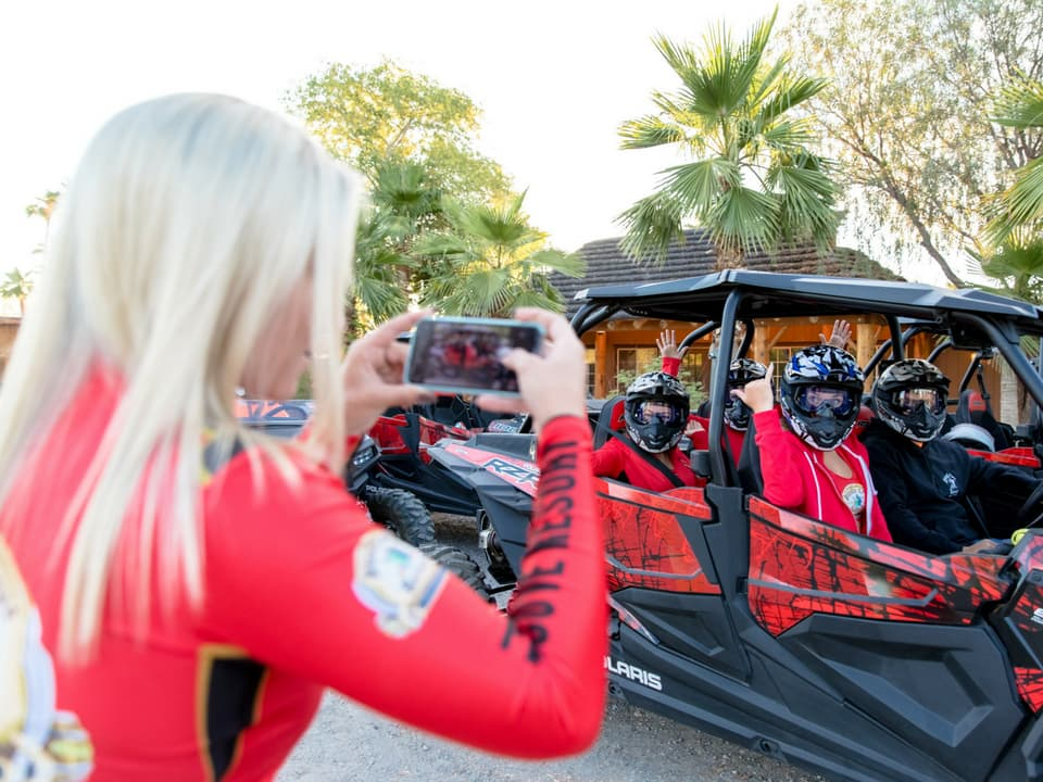 Pirate Cove girls taking a picture of riders in a RZRd
