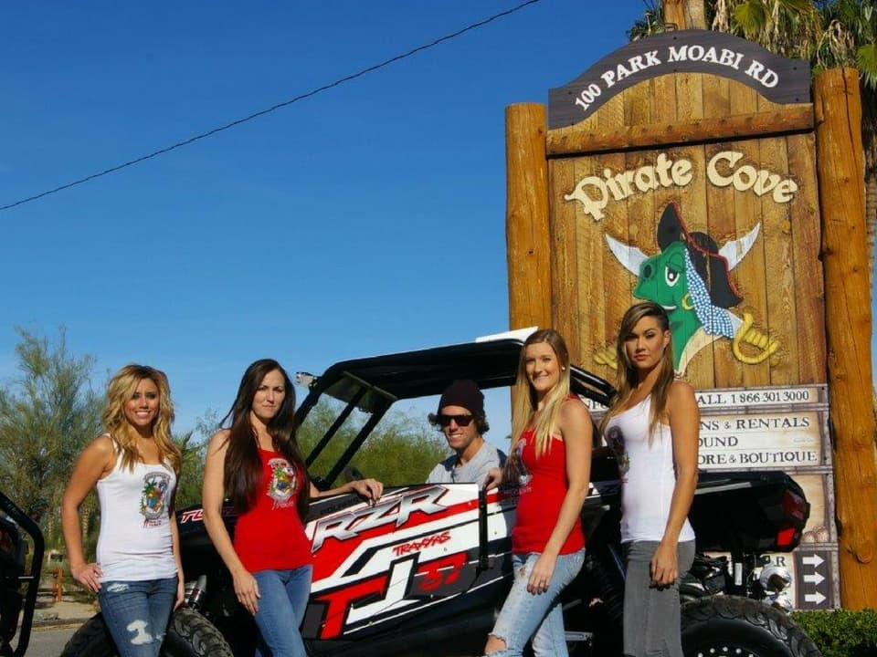 Customers and a RZR in front of the Pirate Cove sign