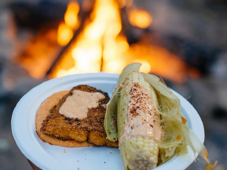 Dinner in front of a campfire at a Wilderness Collective trip