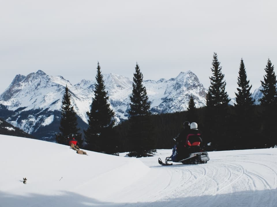 Guests on Polaris Snowmobiles with Silverton, CO mountains in the background