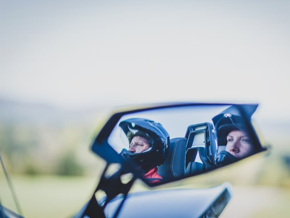Guests in the mirror of a Polaris Slingshot