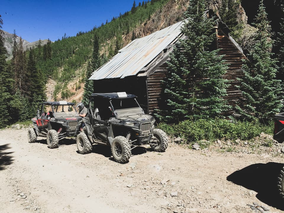 Polaris RZRs parked on the trail