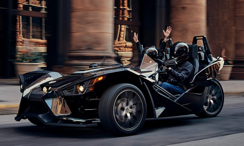 guests riding a Polaris Slingshot with passengers hands in the air