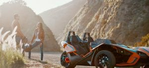guest standing next to parked Polaris Slingshot in a valley