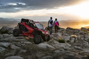 guests standing next to Polaris RZR PRO XP parked on a rocky hill side