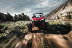 Polaris RZR PRO XP driving through a forested mountainside trail