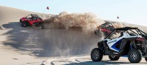 guests riding Polaris RZR PRO XP's up and down sand dunes
