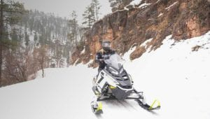 Influencers from Getting Stamped riding Polaris Snowmobiles on an Adventure in Black Hills