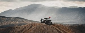 guest and Polaris RZR parked at the top of a sand hill in the middle of the desert