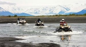 guests driving Polaris Sportsman through large puddles of water in front of scenic Alaska mountains
