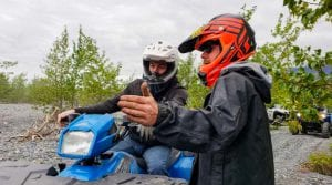 tour guide instructing guest on riding a Polaris Sportsman