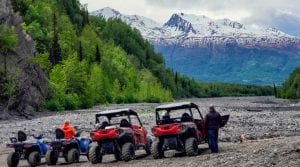 parked off-road vehicles in front of a scenic mountain view of the mountain range in Alaska