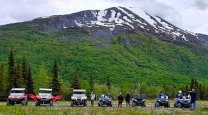 off-road vehicles parked at the bottom of a mountain in Alaska