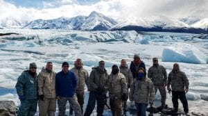 guests posing in front of a scenic background of glaciers and mountains in Alaska