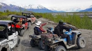 guests on their off-road vehicles looking over the mountain range in Alaska