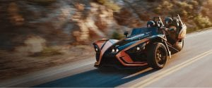 guest driving a Polaris Slingshot down a highway