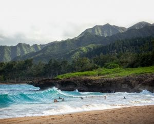 guests swimming in the ocean in front of a scenic mountain range in Hawaii