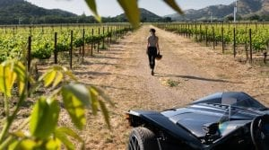 woman walking down rows of a vineyard away from a parked Polaris Slingshot