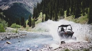 Polaris RZR driving through a large puddle in the Rocky Mountains
