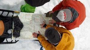 aerial view of guests looking a snowmobile trail map