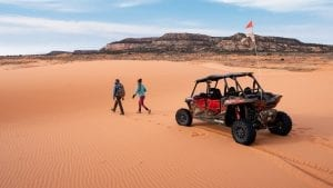 guests walking in the sand dunes next to a Polaris RZR