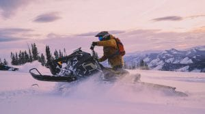 guest riding a Polaris Snowmobile in the snow covered mountains