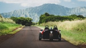 Polaris Slingshot driving down a back road in front of a scenic mountain range in Hawaii
