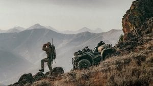 a hunter looking over the mountain range with his hunting equipment on a Polaris Sportsman