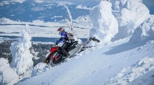 guest riding a Polaris RMK Snowmobile down the mountain in Yellowstone National park