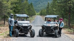 Part Time Tourists posing next to Polaris RZR's during their off-road ride