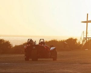 Polaris Slingshot driving down a road during the sunset