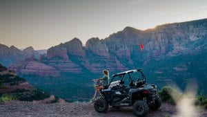 Guest posing by a Polaris RZR 900 overlooking Red Rock in Sedona Arizona