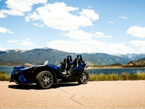Polaris Slingshot parked along a body of water surrounded by the Rocky Mountains