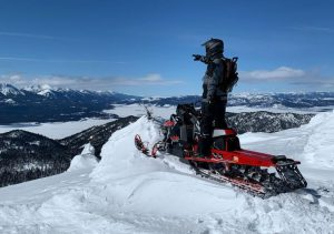 guest-on-a-Polaris-Snowmobile-overlooking-the-snowy-mountains